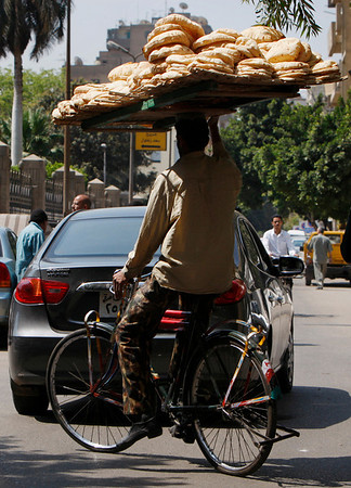 An Egyptian worker uses a bicycle while delivering bread supplies to customers in Cairo, Egypt, Sunday, May 2, 2010.  Many Egyptian workers and employees are performing sit in protests to mark international worker's day, demanding better work conditions and higher wages. (AP Photo/Nasser Nasser)
