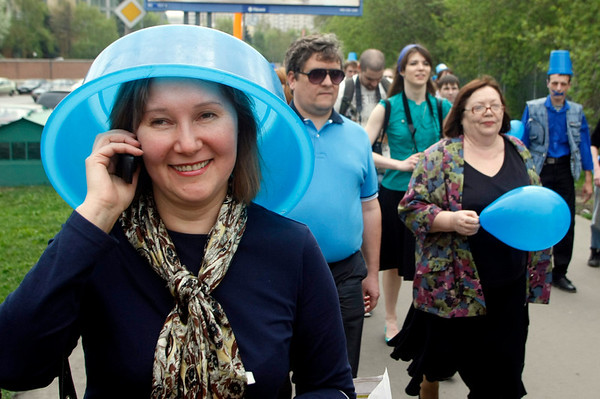 """Members of the new """"Society of blue buckets"""" who wear blue buckets of all shapes and sizes as they gather in Moscow to take part in an unauthorized  flashmob event against flashing blue lights which became a symbol of powerful elite representatives whose cars break all traffic rules, Russia, on Sunday, May 2, 2010. Flashmob participants who several weeks ago formed a Society of blue buckets brought blue buckets of various size to imitate cars with flashing blue organizers of flashmob says that they decided to protest against """"the fact that all people are equal and some people are an exception"""". (AP Photo/Mikhail Metzel)"""