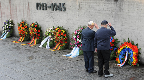 Two men salute in front of wreaths at the former concentration camp in Dachau, southern Germany, on Sunday, May 2, 2010.  Some hundreds of people gathered at Dachau to commemorate the liberation of the Nazi concentration camp 65-years ago. (AP Photo/dapd/Christof Stache)