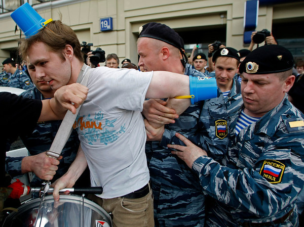"""Riot police, officers detain a member of the new """"Society of blue buckets"""" who wear blue buckets as they gather in Moscow to take part in an unauthorized  flashmob event against flashing blue lights which became a symbol of powerful elite representatives whose cars break all traffic rules, Russia, on Sunday, May 2, 2010. Flashmob participants who several weeks ago formed a Society of blue buckets brought blue buckets of various size to imitate cars with flashing blue organizers of flashmob says that they decided to protest against """"the fact that all people are equal and some people are an exception"""".(AP Photo/Mikhail Metzel)"""