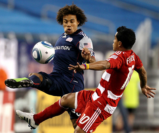 New Engalnd Revolution's Kevin Alston battles FC Dallas' David Ferreira, right for the ball during the first half of a MLS soccer game at Gillette Stadium in Foxborough, Mass. Saturday, May 1, 2010. (AP Photo/Winslow Townson)