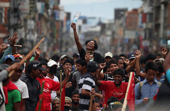 Supporters of Communist Party of Nepal (Maoist) dance on a patriotic song as they block a road in Katmandu, Nepal, Sunday, May 2, 2010. Opposition supporters armed with bamboo sticks enforced a general strike that closed transportation, schools and markets across Nepal on Sunday to demand Prime Minister Madhav Kumar Nepal's resignation. (AP Photo/Altaf Qadri)