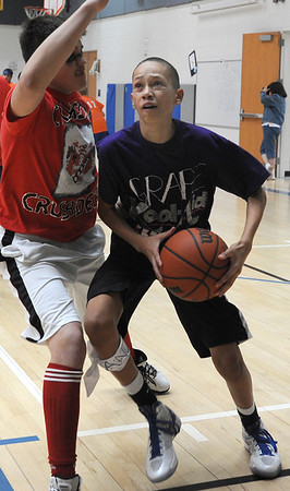 Andrew Martin, right, Grape Kool Aid, goes to the basket against Noah Dohm, Crimson Crusaders during the eighth-grade Roundball Rukus 2012 at  Broomfield Heights Middle School on Thursday.<br /> March 15,  2012 <br /> staff photo/ David R. Jennings