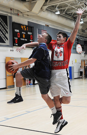Chase Arnold, Wolf Pack, goes to the basket against Noah Dohm, Crimson Crusaders, during the eighth-grade Roundball Rukus 2012 at  Broomfield Heights Middle School on Thursday.<br /> March 15,  2012 <br /> staff photo/ David R. Jennings