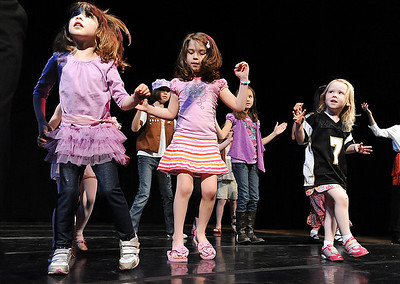 Ellie Stillman, 3, left, Grace Leone, 5, and Jacqueline Fairbairn, 4, dance on stage with Dawn Fay, associate artistic director, during Ballet Nouveau Colorado's young person's guide to dance at the Auditorium on Satuday. March 24, 2012  staff photo/ David R. Jennings