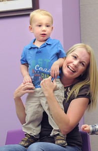 Jett Sloan, 17 months-old, stands on the lap of  his mother,  Malissa,  while listening to stories and music during Thursday's Baby Story Time at the Children's Library at Mamie Doud Eisenhower Public Library. June 9, 2011 staff photo/David R. Jennings