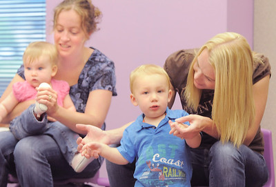 Carole Elges with her daughter Joslyn, 9 months-old, left, and Malissa Sloan with her son Jett, 17 months-old, gesture to a song during Thursday's Baby Story Time at the Children's Library at Mamie Doud Eisenhower Public Library. June 9, 2011 staff photo/David R. Jennings