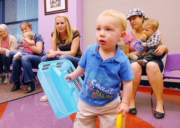 Jett Sloan, 17 months-old, carries a basket to gather musical rattles during Thursday's Baby Story Time at the Children's Library at Mamie Doud Eisenhower Public Library.<br /> June 9, 2011<br /> staff photo/David R. Jennings