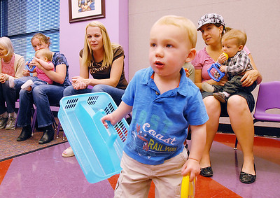 Jett Sloan, 17 months-old, carries a basket to gather musical rattles during Thursday's Baby Story Time at the Children's Library at Mamie Doud Eisenhower Public Library. June 9, 2011 staff photo/David R. Jennings