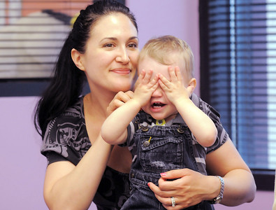 Holden May, 15 months-old, hides his face while playing a game with his mother Karen during Thursday's Baby Story Time at the Children's Library at Mamie Doud Eisenhower Public Library. June 9, 2011 staff photo/David R. Jennings