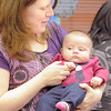 Kristin Miesel holds her daughter Elena, 3 1/2 months-old, while listening to songs during Thursday's Baby Story Time at the Children's Library at Mamie Doud Eisenhower Public Library.<br /> June 9, 2011<br /> staff photo/David R. Jennings