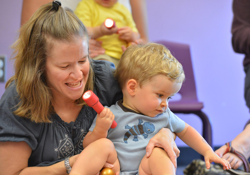 be0719babystory06.JPG Kathy Knight with her son Owen, 14 months old,  play with a flashlight as a story is read  during Baby Story Time at the children's library on Thursday.<br /> <br /> <br /> July 12, 2012<br /> staff photo/ David R. Jennings
