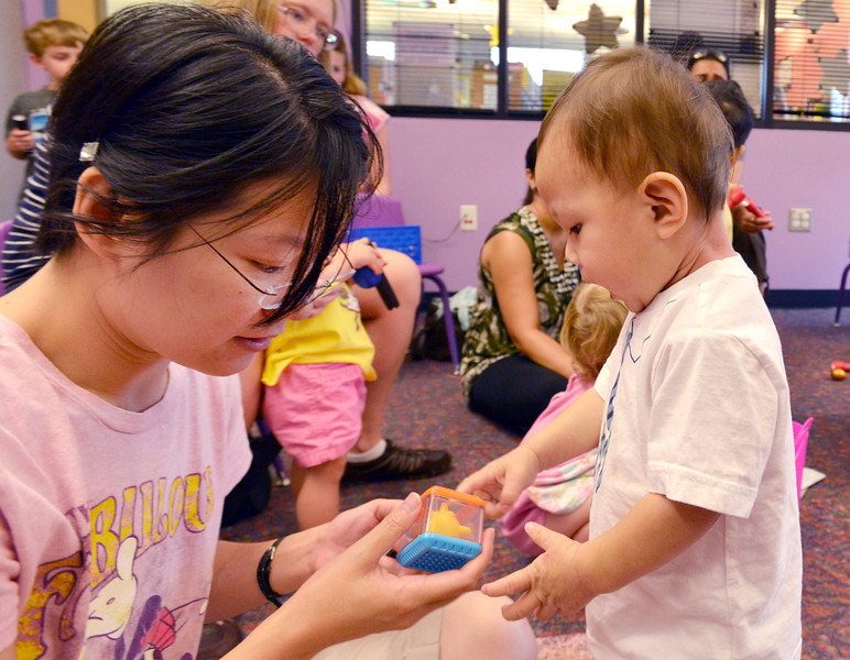 be0719babystory09.JPG Shuang Wang, left, and her son Justin, 20 months-old, play with a toy  during Baby Story Time at the children's library on Thursday.<br /> <br /> July 12, 2012<br /> staff photo/ David R. Jennings