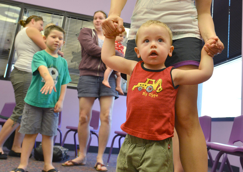 be0719babystory07.JPG Wyatt Smith, 1 1/2, moves to a song with his mother Jaime during Baby Story Time at the children's library on Thursday.<br /> <br /> July 12, 2012<br /> staff photo/ David R. Jennings