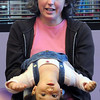 Gemma Amaria, 15 months-old, is held upside down  by her aunt Kelly Kehmeier for an exercise during a story at Baby Story Time at Mamie Doud Eisenhower Public Library Children's Library on Thursday.  <br /> April 8, 2010<br /> Staff photo/David R. Jennings