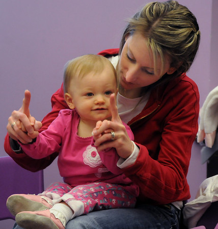 Jen Seifried motions with her daughter Kylie, 1, while listening to a song during  Baby Story Time at Mamie Doud Eisenhower Public Library Children's Library on Thursday.  <br /> <br /> April 8, 2010<br /> Staff photo/David R. Jennings