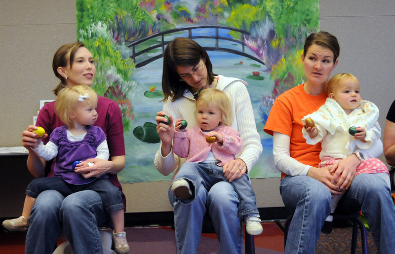 Caroline Benzley and daughter Clara, 19 months-old, left, Jamie Ward and daughter Callie, 18 months-old, and Kate Hansen and daughter Lucy, 18 months-old, listens to stories during  Baby Story Time at Mamie Doud Eisenhower Public Library Children's Library on Thursday.  <br /> <br /> April 8, 2010<br /> Staff photo/David R. Jennings