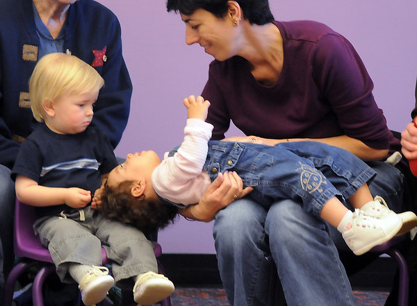 Gina Amaria, right, holds her daughter Gemma, 15 months-old, upside down while looking at Isaac McGraw, 18 months-old, during Baby Story Time at Mamie Doud Eisenhower Public Library Children's Library  on Thursday. <br /> <br /> April 8, 2010<br /> Staff photo/David R. Jennings