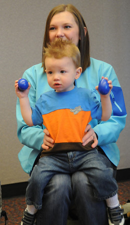 Aiden Archibald, 1 1/2, shakes egg shaped rattles while sitting on the lap of his mother, Kelli, during  Baby Story Time at Mamie Doud Eisenhower Public Library Children's Library  on Thursday.  <br /> <br /> April 8, 2010<br /> Staff photo/David R. Jennings