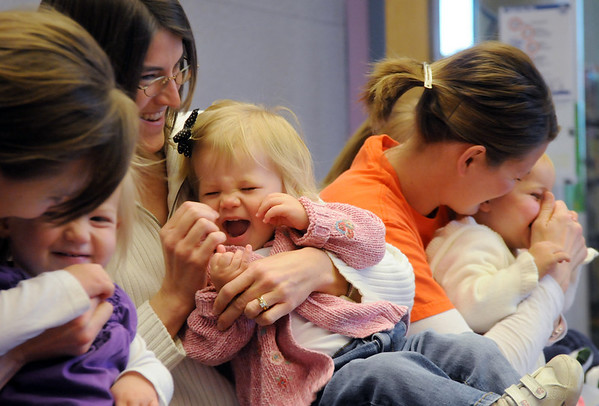 Clara Benzley, 19 months-old, left, Callie Ward, 18 months-old, and Lucy Hansen, 18 months-old, giggle as their mothers touch their noses during  Baby Story Time at  Mamie Doud Eisenhower Public Library Children's Library  on Thursday.  <br /> <br /> April 8, 2010<br /> Staff photo/David R. Jennings