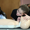 Avery Bohn, 11, right, listens for breath on a child dummy while Olivia Cornejo, 11, watches as they learn rescue breathing during the American Red Cross babysitter class at the Broomfield Community Center on Saturday.<br /> <br /> January 09, 2010<br /> Staff photo/David R. Jennings