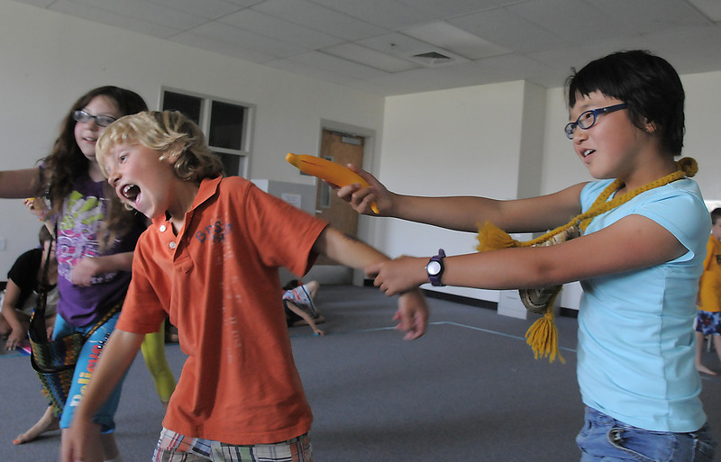 Mowgli, Bode Hogan, 7, center, is captured by the monkeys, Lily McKeralt-Gould, 9, right, and Kianna Duran, 9, during rehearsal for  BackStory Theater Academy's production of the Jungle Book at Aspen Creek K-8 on Friday.<br /> <br /> July 8, 2011<br /> staff photo/ David R. Jennings