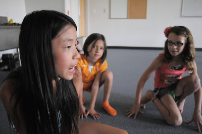 Jade Martin, 11, left, playing Shere Khan, orders the jackals, Alexandra Gomez, 8, and Christina Perez, 9, to search for Mowgli during rehearsal for  BackStory Theater Academy's production of the Jungle Book at Aspen Creek K-8 on Friday.  July 8, 2011 staff photo/ David R. Jennings