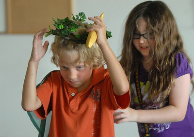 Bobe Hogan, 7, ( Mowgli) receives a crown as king of the monkeys by Kianna Duran, 9, during rehearsal for  BackStory Theater Academy's production of the Jungle Book at Aspen Creek K-8 on Friday.  July 8, 2011 staff photo/ David R. Jennings