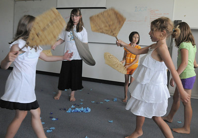 Mira Dondelinger, 10, center, playing the girl from the village, celebrates with the villages for a festival during rehearsal for  BackStory Theater Academy's production of the Jungle Book at Aspen Creek K-8 on Friday.  July 8, 2011 staff photo/ David R. Jennings