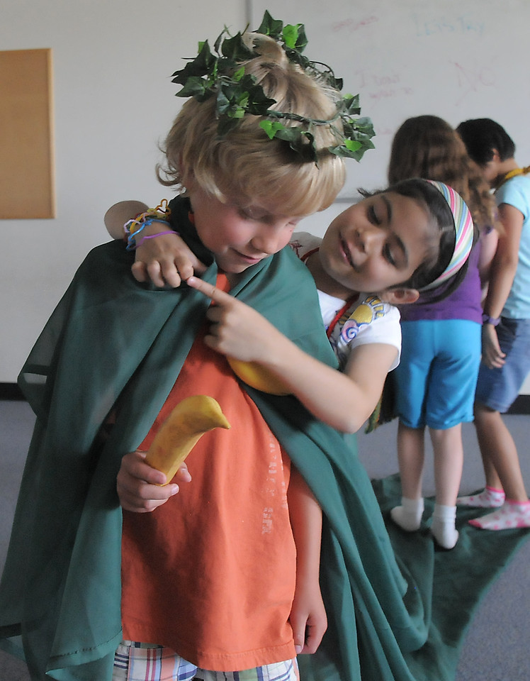 Gabby Lovatto, 6, ( a monkey) puts a robe on Bode Hogan, 7, (Mowgli) during rehearsal for  BackStory Theater Academy's production of the Jungle Book at Aspen Creek K-8 on Friday.<br /> <br /> July 8, 2011<br /> staff photo/ David R. Jennings