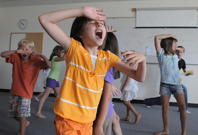 Alexandra Gomez, 8, plays at being an animal during the warm-up before the rehearsal for  BackStory Theater Academy's production of the Jungle Book at Aspen Creek K-8 on Friday.  July 8, 2011 staff photo/ David R. Jennings