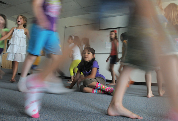 Isabella Martinez, 7, sits on the floor while the cast dances around her  during rehearsal for  BackStory Theater Academy's production of the Jungle Book at Aspen Creek K-8 on Friday.<br /> <br /> July 8, 2011<br /> staff photo/ David R. Jennings