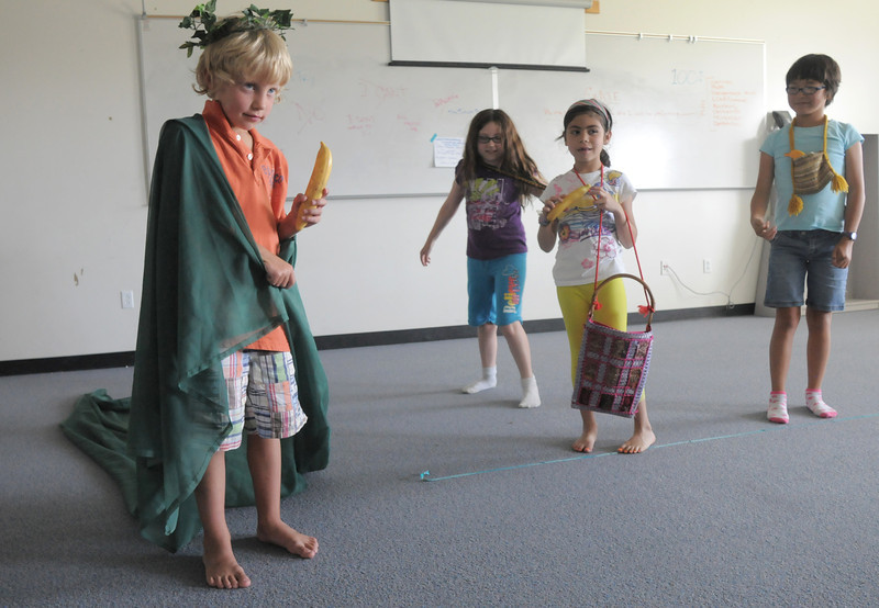 Bode Hogan, 7, left, playing Mowgli, wears a crown and robe after being crowned king of the monkeys by Kianna Duran, 9, Gabby Lovatto, 6, and Lily xx, 9, during rehearsal for  BackStory Theater Academy's production of the Jungle Book at Aspen Creek K-8 on Friday.<br /> <br /> July 8, 2011<br /> staff photo/ David R. Jennings