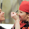 Assistant director Abbie Griffith puts makeup on Noah Mowry, 7, playing a robber for the Backstory Theatre Academy's Make Believe and Beyond class production of The Bremen Town Musicians at the Audi on Tuesday.<br /> <br /> March 1, 2011<br /> staff photo/David R. Jennings