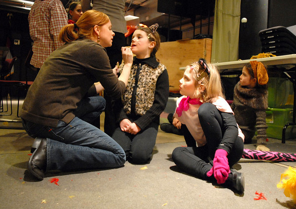 Assistant director Abbie Griffith, left, puts last minute makeup on cat #1, Sara Carleo, 7, while fellow cat Lily Gregory, 5, watches before the Backstory Theatre Academy's Make Believe and Beyond class production of The Bremen Town Musicians at the Audi on Tuesday.<br /> <br /> March 1, 2011<br /> staff photo/David R. Jennings