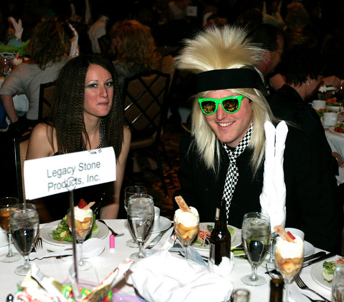 Amanda Dunwoodie, left, and Seth Howerton enjoy dinner in their 80's costumes at the Totally Awesome 80's Bal Swan Ball on Saturday night at the Omni Interlocken Hotel Ballroom. <br /> March 5, 2011<br />  photo/Matt Kelley