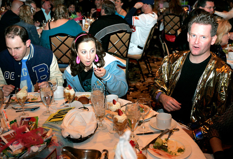 Brian Cavanaugh, left, Jennifer Sadler, and Mike Day enjoy dinner in their 80's costumes at the Totally Awesome 80's Bal Swan Ball on Saturday night at the Omni Interlocken Hotel Ballroom.<br /> March 5, 2011<br />  photo/Matt Kelley