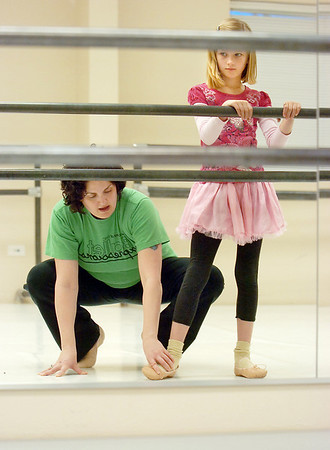 """Instructor Heather Sutton, left, helps Kara Newton, 8, move into a ballet position at the bar during Ballet Nouveau Colorado's Ballet Expressions classes for the physically and mentally challenged students on Thursday at the BNC studios.<br /> For more photos please see  <a href=""""http://www.broomfieldenterprise.com"""">http://www.broomfieldenterprise.com</a>.<br /> January 12, 2012<br /> staff photo/ David R. Jennings"""
