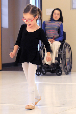 """Riley Tuttle, 7, dances across the floor while intern Sasha Galikeeva watches in the background during Ballet Nouveau Colorado's Ballet Expressions classes for the physically and mentally challenged students on Thursday at the BNC studios.<br /> For more photos please see  <a href=""""http://www.broomfieldenterprise.com"""">http://www.broomfieldenterprise.com</a>.<br /> January 12, 2012<br /> staff photo/ David R. Jennings"""