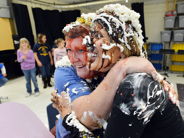 Mountain View Elementary School principal Tracey Amend, right, and assistant principal Shelley Stetler give each other a hug after being covered in banana split toppings by students during an assembly at the school on Friday. <br /> <br /> November 30, 2012<br /> staff photo/ David R. Jennings