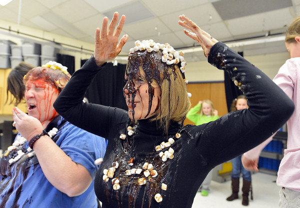 Mountain View Elementary School principal Tracey Amend, right, arranges mashmallows on her head while assistant principal Shelley Stetler takes a taste of the banana split toppings poured on their heads by students during an assembly at the school on Friday. The principals agreed to the stunt if 100 or more students ran in a fundraising event in October.<br /> <br /> November 30, 2012<br /> staff photo/ David R. Jennings