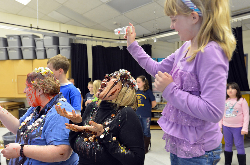 Mountain View Elementary School principal Tracey Amend, right, tries to take a taste of the sprinkles pured on her head by first grader Sammie Marietta during an assembly at the school on Friday. The principals agreed to the stunt if 100 or more students ran in a fundraising event in October.<br /> <br /> November 30, 2012<br /> staff photo/ David R. Jennings