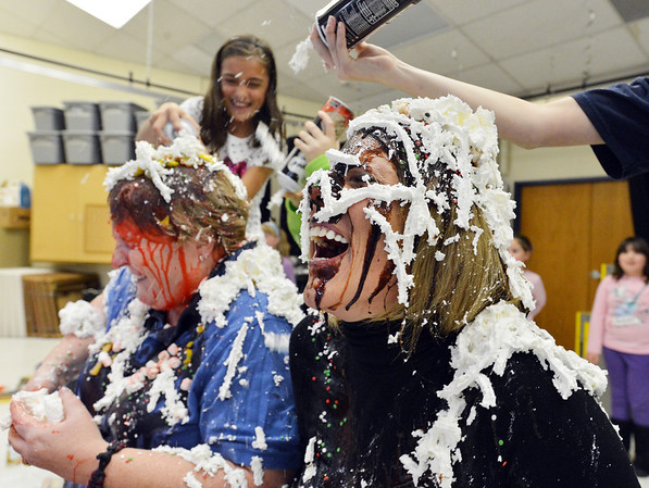 Mountain View Elementary School principal Tracey Amend, right, and assistant principal Shelley Stetler have whipped cream sprayed on their heads for a banana split topping by 5th grader Ashley Becker, far left, and 4th grader Brett Kaufman during an assembly at the school on Friday. The principals agreed to the stunt if 100 or more students ran in a 1k and 5k fundraising event last October.<br /> <br /> November 30, 2012<br /> staff photo/ David R. Jennings