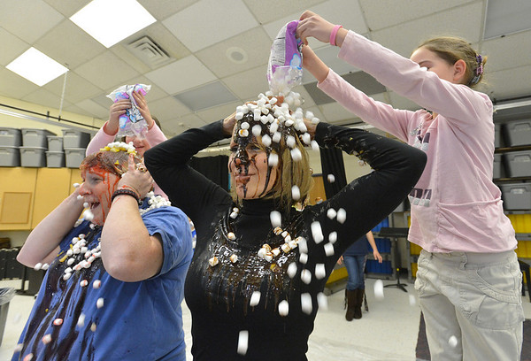 Mountain View Elementary School principal Tracey Amend, right, and assistant principal Shelley Stetler have banana split toppings of marshmallows poured on their heads by second grader Reagan Petit, left,  and 3rd grader Emily Kippes during an assembly at the school on Friday. <br /> <br /> November 30, 2012<br /> staff photo/ David R. Jennings