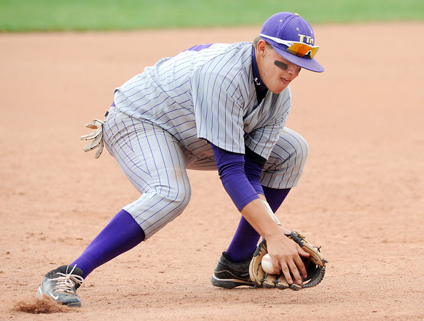 Holy Family's third baseman, Jay Elliott, scoops up a ground ball hit by  Faith Christian during Saturday's game at Faith Christian.<br /> <br /> April 14, 2012 <br /> staff photo/ David R. Jennings