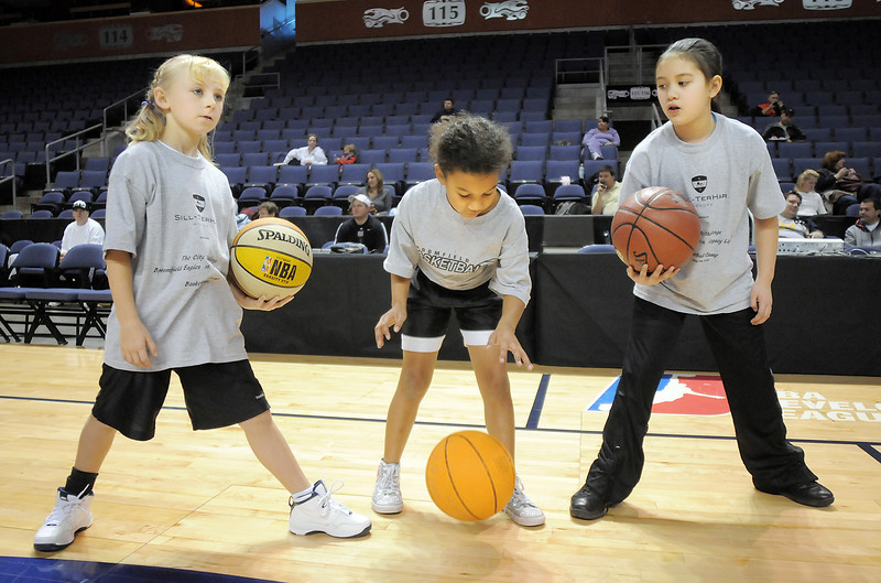 Kara Zila, 9, left, with Alyssa Remy, 8, and Amelia Walker, 8, try their skill at dribbling the basketball during the basketball clinic before Saturday's Broomfield  Vs. Legacy girls and boys games at the 1stBank Center.<br /> January 8, 2011<br /> staff photo/David R. Jennings