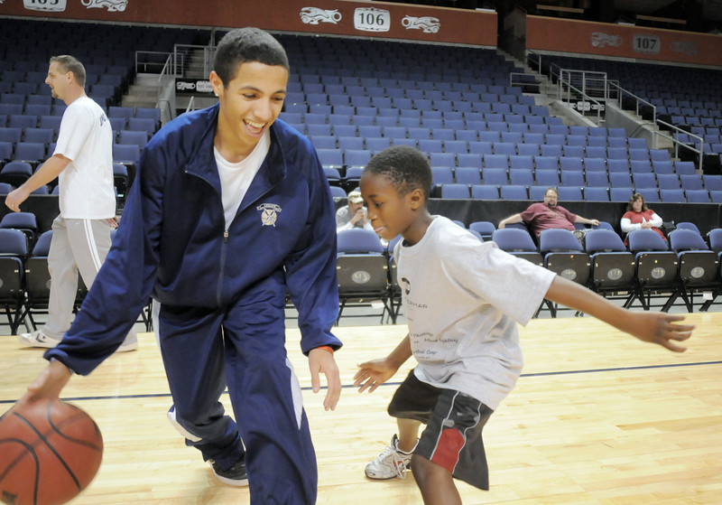 Mawold Easton, 9, right, tries to get the ball from Legay's Marcus Riddick during the basketball clinic before Saturday's Broomfield  Vs. Legacy girls and boys games at the 1stBank Center.<br /> January 8, 2011<br /> staff photo/David R. Jennings