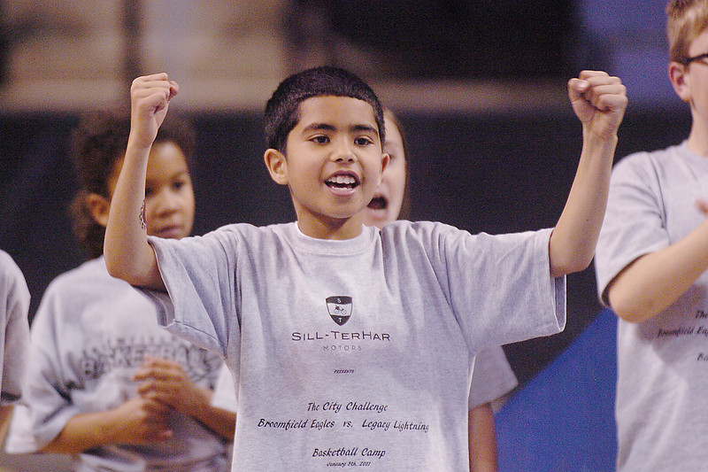 Antonio Martinez, 10, cheers while watching a game of shooting baskets during the basketball clinic before Saturday's Broomfield  Vs. Legacy girls and boys games at the 1stBank Center. % students were chosen for best cheering to receive a basketball. <br /> January 8, 2011<br /> staff photo/David R. Jennings