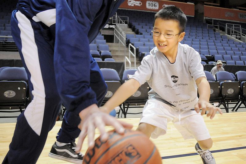 Trenton Homchanh, 8, tries to take the ball from Legacy's Mike Lehnerz during the basketball clinic before Saturday's Broomfield  Vs. Legacy girls and boys games at the 1stBank Center. <br /> January 8, 2011<br /> staff photo/David R. Jennings