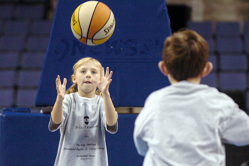 Kara Zila, 9, catches the ball thrown by Joren Moos, 8, during the basketball clinic before Saturday's Broomfield  Vs. Legacy girls and boys games at the 1stBank Center.<br /> January 8, 2011<br /> staff photo/David R. Jennings